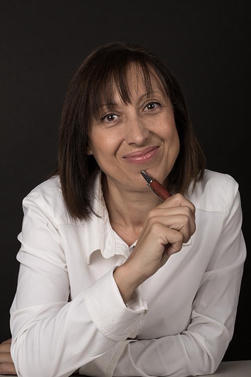 Fotografía de Inma Vives sonriente con un bolígrafo en la mano.